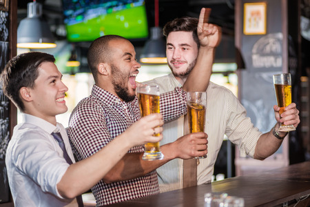 Mannen fans schreeuwen en het kijken naar voetbal op tv en drinken bier. Drie andere mannen het drinken van bier en plezier samen in de bar terwijl er een voetbalwedstrijd op tv Stockfoto