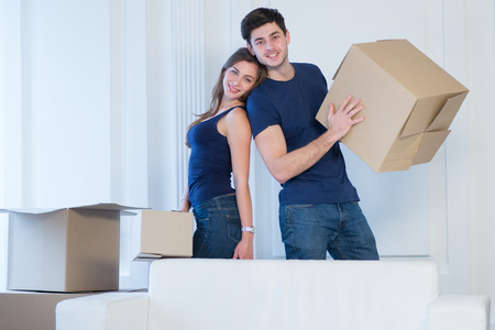 shifting: Moving, repairs, new life. Couple in love enjoys a new apartment and keep the box in his hands while young and beautiful couple in love sitting on the couch in an empty apartment among boxes