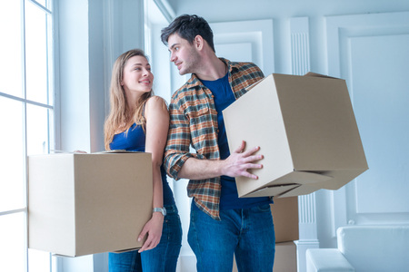 Moving to a new life. A girl and a guy holding boxes for moving the hands and smiling at the camera while a couple in love standing at the window among boxes Banque d'images