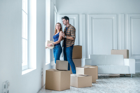 Bewegende, reparaties, nieuw leven. Paar in liefde geniet van een nieuw appartement en houden de doos in zijn handen terwijl de jonge en mooie paar in liefde zittend op de bank in een leeg appartement tussen dozen