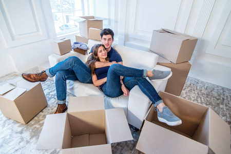 Moving home and repair of a new life. Couple in love pulls things out of boxes for moving while man and woman sitting among the boxes in an empty apartment Standard-Bild
