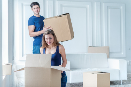 shifting: Moving home and repair of a new life. Couple in love pulls things out of boxes for moving while man and woman sitting among the boxes in an empty apartment Stock Photo