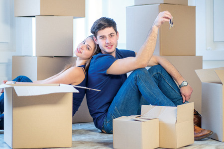 shifting: Moving, repairs, new keys to the apartment. Couple girl and the guy holding the keys to the apartment while man and woman sitting on the floor among the boxes in an empty apartment
