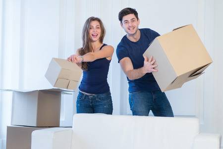 shifting: New life in a new home. Couple in love enjoys a new apartment and keep the box in his hands while young and beautiful couple in love sitting on the couch in an empty apartment among boxes