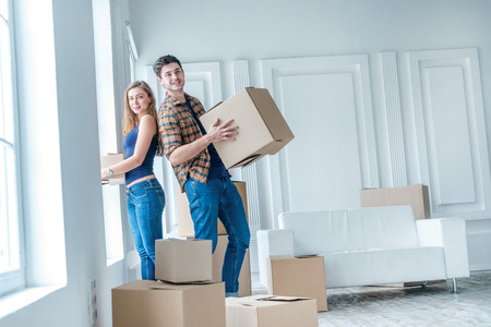 New life. Couple in love moving and keep a box in his hands and looking at the camera while a young and beautiful couple in love sitting on the couch in an empty apartment among boxes