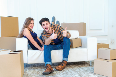 shifting: The joy of moving into the house. A loving couple holding box in hands and looking at the camera while a young and beautiful couple in love sitting on the couch in an empty apartment among boxes Stock Photo