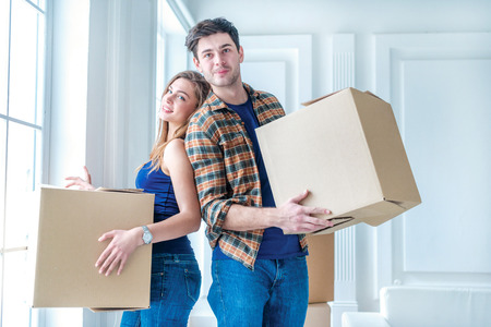 shifting: Dream come true, moving. Loving couple enjoys a new apartment and keep the box in his hands while young and beautiful couple in love sitting on the couch in an empty apartment among boxes