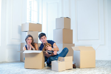 shifting: New repair and relocation. Loving couple enjoys a new apartment and keep the box in his hands while young and beautiful couple in love sitting on the couch in an empty apartment among boxes Stock Photo