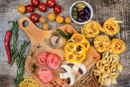 Mix different colored raw whole grain pasta and noodles. Organic pasta of different types of tubes up shells on a wooden table with tomatoes and mushrooms. Photo products on top