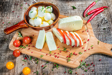 gaudy: Feta cheese or mozzarella cheese is sliced on a wooden board with tomatoes and red pepper. Feta cheese or mozzarella cheese decorated with red pepper.