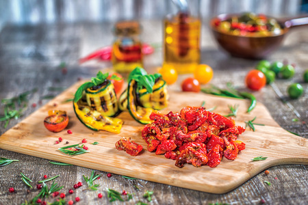 Dish of twisted zucchini and sun-dried tomatoes on the board. Roll the zucchini closeup decorate tomatoes and red bell pepper and green olives with olive oil Standard-Bild
