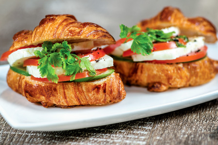 mozzarella cheese: Croissants with cheese feta and mozzarella, pesto and roasted zucchini and bell pepper. Stock Photo