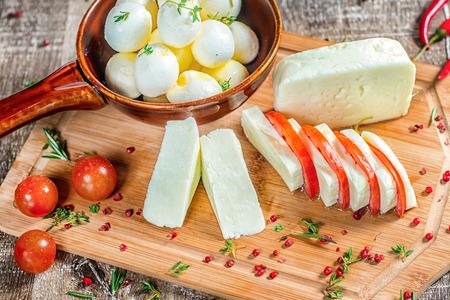 queso de cabra: Queso feta o queso mozzarella se rebana en una tabla de madera con los tomates y el pimiento rojo. Queso feta o queso mozzarella decorado con pimiento rojo.
