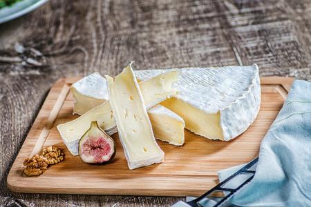 queso: Queso brie rebanada en una mesa de madera y trozos de higos