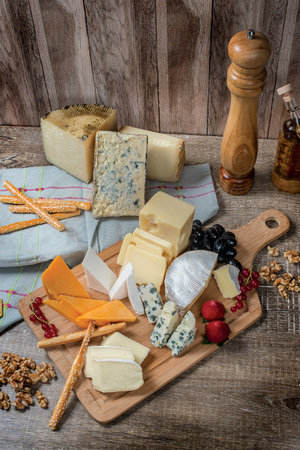 cheese plate: Cheese heaven. Cheese Mix Cheese brie, gouda cheese, blue cheese, cheese marmezan, orange cheese on a wooden board Stock Photo