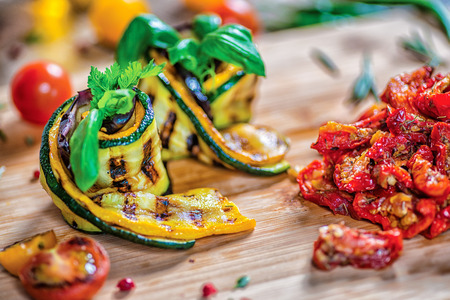 Dish of twisted zucchini and sun-dried tomatoes. Roll the zucchini closeup decorate tomatoes and red bell pepper. Фото со стока
