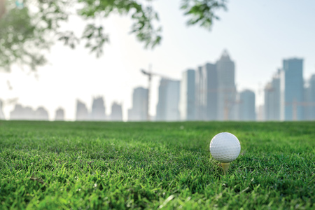 Professionele golf. Golf bal op de tee van een golfbal op het groene gras op de golfbaan tegen de achtergrond van de stad wolkenkrabbers