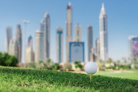 De golf dag. Golf bal op de tee een golfbaan voor de bal op het gras op een golfbaan op de achtergrond van de stad wolkenkrabbers