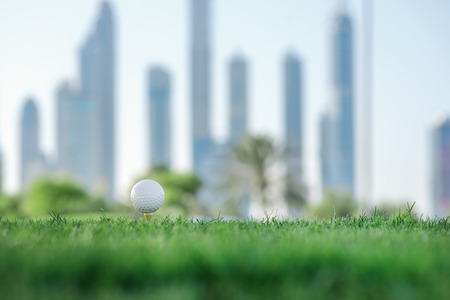 Professional golf. Golf ball is on the tee for a golf ball on the green grass of the golf course against the background the city skyscrapers