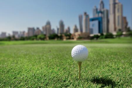 Professionals golfen. Golf bal op de tee van een golfbal op het gras op een golfbaan op de achtergrond van de stad wolkenkrabbers