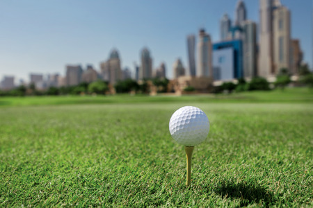 Professionals play golf. Golf ball is on the tee for a golf ball on the grass on a golf course on the background of the city skyscrapers