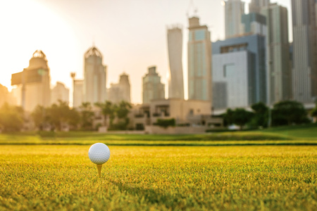 Playing golf at sunset. Golf ball is on the tee for a golf ball on the green grass of the golf course against the background the city skyscrapers at sunset Stock Photo