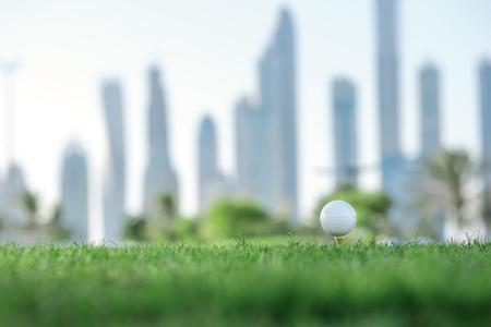 Dag van de golf. Golf bal op de tee van een golfbal op het groene gras op de golfbaan tegen de achtergrond van de skyline van de stad