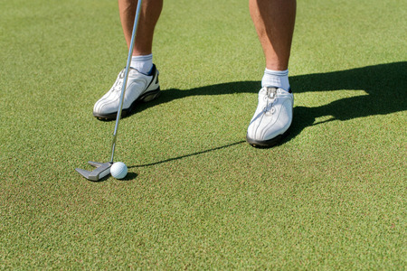 The golf day. Golfer holding a a club and is going to hit the golf ball. Stock Photo