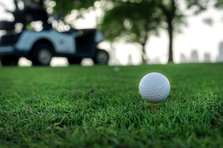 Playing golf and a golf cart. Golf ball is on the tee for a golf ball on the green grass of the golf course against the background the city's skyscrapers and golf carts