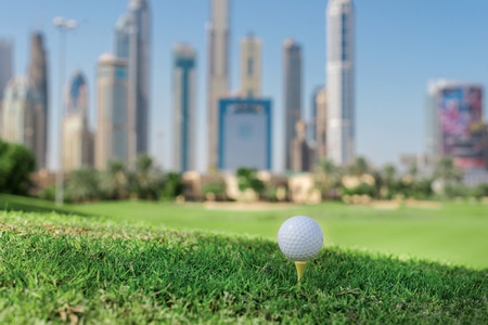 The golf day. Golf ball is on the tee A golf course for the ball on the grass on a golf course on the background of the city skyscrapers