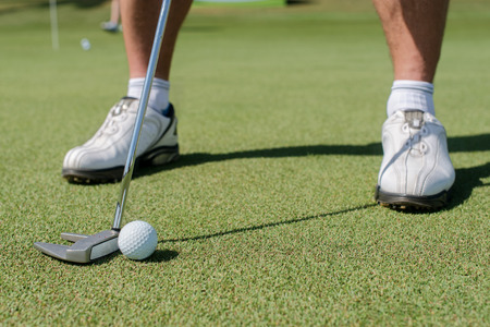 Professionals play golf. Golfer holding a a club and is going to hit the golf ball. Stock Photo