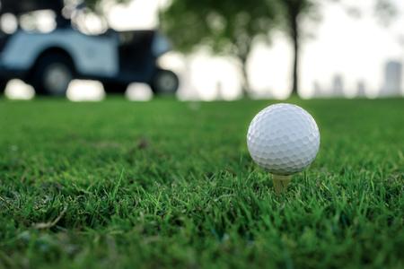 Golfen en een golfkar. Golf bal op de tee van een golfbal op het groene gras op de golfbaan tegen de achtergrond van de wolkenkrabbers van de stad en golfkarretjes