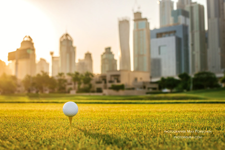 Golfen bij zonsondergang. Golf bal op de tee van een golfbal op het groene gras op de golfbaan tegen de achtergrond van de stad wolkenkrabbers bij zonsondergang Stockfoto