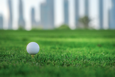 Day of golf. Golf ball is on the tee for a golf ball on the green grass of the golf course against the backdrop of the city skyline