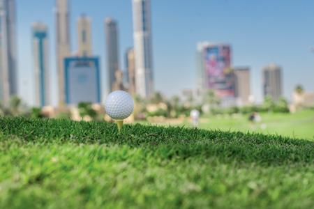De beste dag voor golfen. Golf bal op de tee van een golfbal op het gras op een golfbaan op de achtergrond van de stad wolkenkrabbers