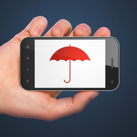 Hand holding smartphone with Umbrella on display. Generic mobile smart phone in hand on dark blue background. photo