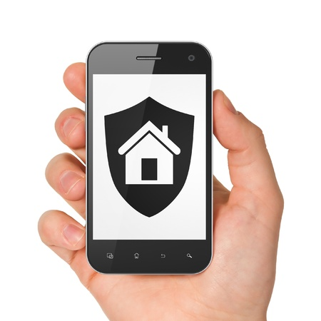 Hand holding smartphone with shield on display. Generic mobile smart phone in hand on white background. photo
