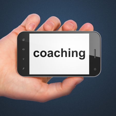 Hand holding smartphone with word coaching on display. Generic mobile smart phone in hand on dark blue background. photo