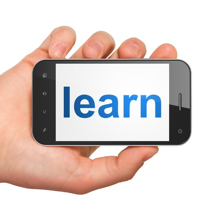 Hand holding smartphone with word learn on display. Generic mobile smart phone in hand on white background. photo