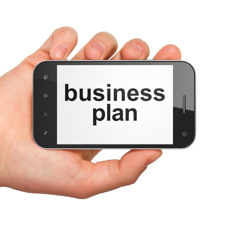 Hand holding smartphone with word business plan on display. Generic mobile smart phone in hand on white background. photo