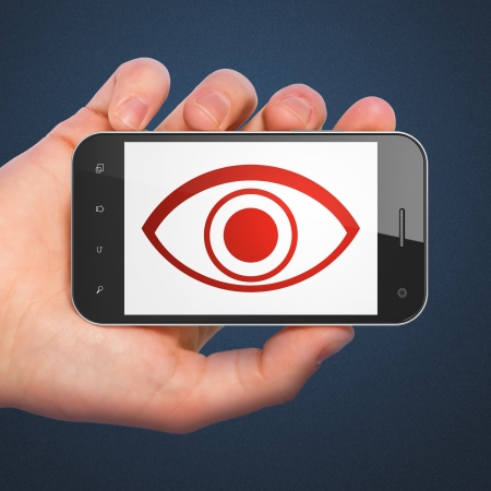 Security concept  hand holding smartphone with Eye on display  Generic mobile smart phone in hand on Dark Blue background Stock Photo - 17549292