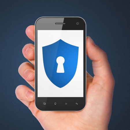 cyber crime: Safety concept  hand holding smartphone with Shield With Keyhole on display  Generic mobile smart phone in hand on Dark Blue background  Stock Photo