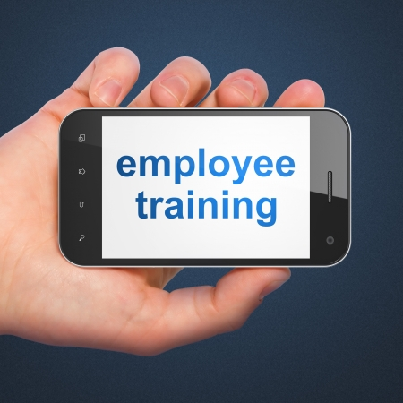 Education concept  hand holding smartphone with word Employee Training on display  Generic mobile smart phone in hand on Dark Blue background  photo