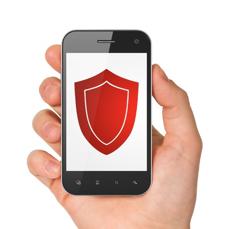 Protection concept  hand holding smartphone with Shield on display  Generic mobile smart phone in hand on White background  Stock Photo - 17549810
