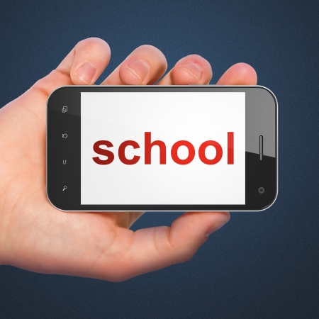 Education concept  hand holding smartphone with word School on display  Generic mobile smart phone in hand on Dark Blue background  photo