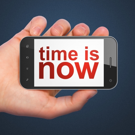 Time concept  hand holding smartphone with word Time is Now on display  Generic mobile smart phone in hand on Dark Blue background  photo