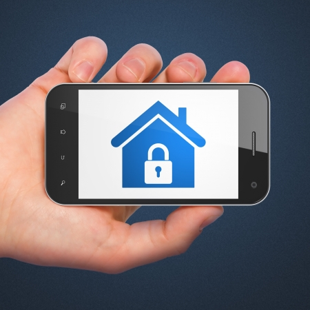 mobile security: Safety concept  hand holding smartphone with Home on display  Generic mobile smart phone in hand on Dark Blue background  Stock Photo