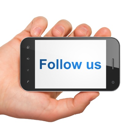 Social media concept  hand holding smartphone with word Follow us on display  Generic mobile smart phone in hand on White background  photo