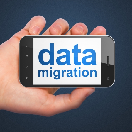 migrating cell: Information concept: hand holding smartphone with word Data Migration on display. Generic mobile smart phone in hand on Dark Blue background.