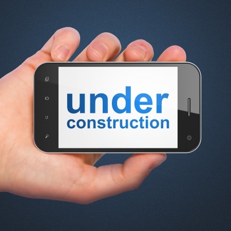SEO web design concept: hand holding smartphone with word Under Construction on display. Generic mobile smart phone in hand on Dark Blue background. photo